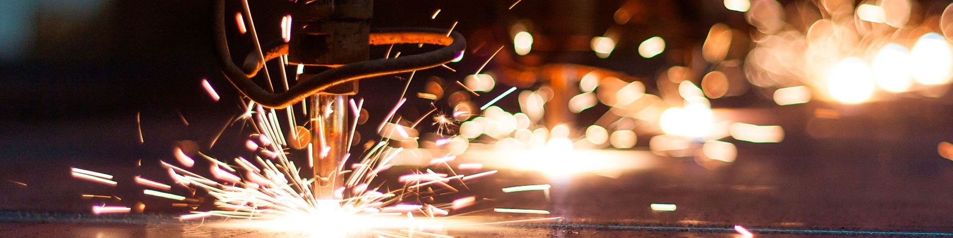 Sparks flying, as an industrial drill hits metal.